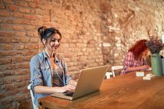 Smiling girl chating on laptop. In cafe royalty free stock photo