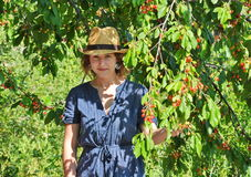 Smiling girl among cherry branches Stock Image
