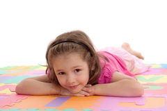 Smiling girl child resting on kids alphabet floor. Girl resting on colorful alphabet floor Mat. Isolated on white Royalty Free Stock Photos