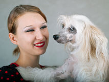 Smiling girl and chinese crested dog. The beautiful smiling girl and chinese crested dog on grey background. Shallow DOF, focus on dog stock images