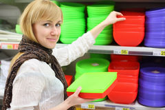 Smiling girl chooses colored plates in shop Stock Image