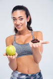 Smiling girl choosing between apple and chocolate Stock Photo