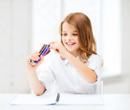 Smiling girl choosing colorful felt-tip pen Stock Photo