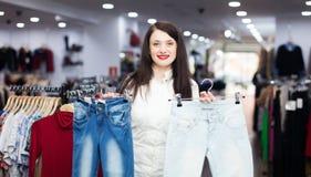 Smiling girl choosing jeans Royalty Free Stock Image