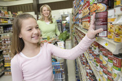 Smiling Girl Choosing Products From Supermarket Shelf Royalty Free Stock Images
