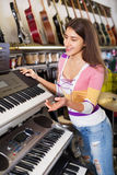 Smiling  girl choosing synthesizer Royalty Free Stock Image
