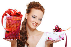 Smiling girl choosing between two gifts Royalty Free Stock Photos