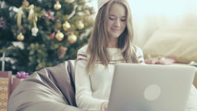 Smiling girl in christmas cap using laptop on soft chair stock video footage