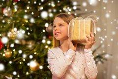 Smiling girl with christmas gift at home royalty free stock photography