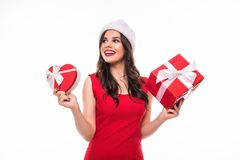 Smiling girl with Christmas gifts in hands Santa`s helper. Girl on dress and Santa`s hat on white background stock photo