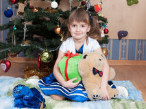 Smiling girl with christmas gifts at christmas tree (6 years) Royalty Free Stock Photography