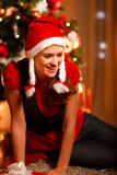 Smiling girl at Christmas tree looking in corner Royalty Free Stock Photos