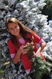 Smiling girl in Christmas tree lot. Girl holding scraps of christmas trees at a christmas tree lot Royalty Free Stock Image
