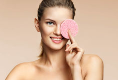 Smiling girl cleaning face with exfoliating sponge Stock Photo