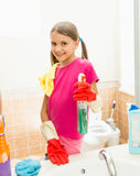 Smiling girl cleaning faucet and mirror at bathroom Royalty Free Stock Images
