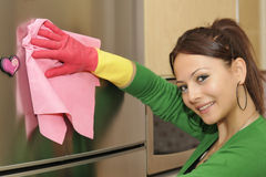 Smiling girl cleaning the house - refrigerator. A casual girl using a disinfectant wipe to clean the refrigerator Royalty Free Stock Photo