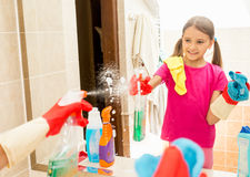 Smiling girl cleaning mirror at bathroom with spray and cloth Royalty Free Stock Photos