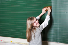 Smiling girl cleaning school blackboard Stock Image