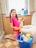 Smiling girl cleaning toilet with brush Royalty Free Stock Photography