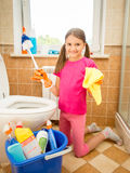 Smiling girl cleaning toilet with brush and rag Stock Images