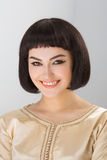 Smiling girl with Cleopatra's make-up and haircut posing in studio. High fashion look. Glamorous closeup portrait of beautiful stylish brunette young woman model royalty free stock images