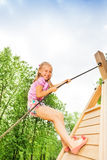 Smiling girl climbs on wooden construction Royalty Free Stock Photography