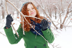 Smiling girl clings to branch with berries. At winter day Royalty Free Stock Photos