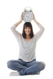 Smiling girl with clock on head in lotus pose Royalty Free Stock Image