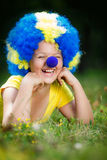 Smiling girl in clown wig with blue nose is lying on the green grass Royalty Free Stock Photos