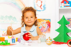 Smiling girl colors New Year ball for Xmas tree. Smiling girl colors New Year ball for Christmas tree while sitting alone at the white table with decorations on Royalty Free Stock Images