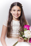 Smiling girl with communion dress holding bouquet of peonies. Royalty Free Stock Images