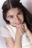 Smiling girl with communion dress holding a rosay Stock Image
