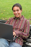 Smiling girl with computer. Young smiling woman sitting with laptop on the bench in the park Stock Images