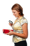 Smiling girl considers a purse through a magnifier Stock Image