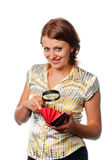 Smiling girl considers a purse through a magnifier Royalty Free Stock Photos