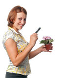 Smiling girl considers violets through a magnifier Royalty Free Stock Photography