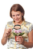 Smiling girl considers violets through a magnifier Royalty Free Stock Image