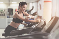 Smiling girl controlling her results in a gym Stock Image