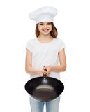 Smiling girl in cook hat giving frying pan Stock Photo