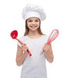 Smiling girl in cook hat with ladle and whisk Stock Photos