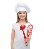 Smiling girl in cook hat with ladle and whisk Royalty Free Stock Photo