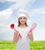 Smiling girl in cook hat with ladle and whisk Royalty Free Stock Images