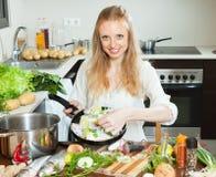 Smiling girl cooking fish  in frying pan at  kitchen Royalty Free Stock Image