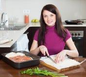 Smiling girl cooking fish pie Royalty Free Stock Image