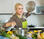 Smiling girl cooking with vegetables Royalty Free Stock Image