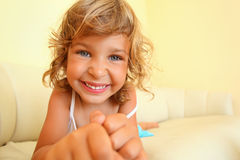 Smiling girl in cosy room, stretches hands forward Stock Photos