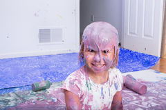 Smiling girl covered in various colors of paint. Smiling girl having fun and covered in various colors of paint in home. Empty bottles lay on the canvas behind stock photo
