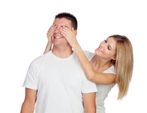 Smiling girl covering his boyfriend's eyes to surprise him Royalty Free Stock Photos
