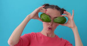 Woman wonders holds Avocado in her hands like eyes. Smiling girl covering his eyes with Avocado. Happy girl with fresh vegetables wonders. Close up girl fool stock video