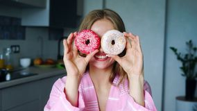 Smiling girl covering his eyes with glazed donuts. Pretty woman having fun